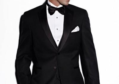 Juodas smokingas su juoda apykakle ir juoda peteliške