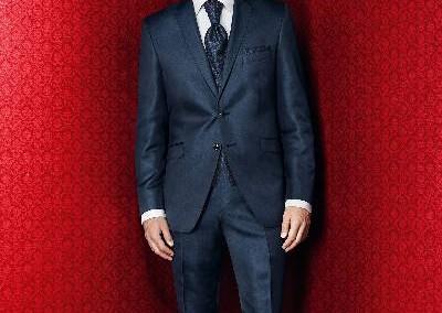 Tamsiai mėlynas dviejų sagų, blizgus kostiumas